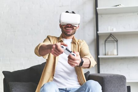 Young smiling man in VR glasses playing video game with joystick, siting on the couch