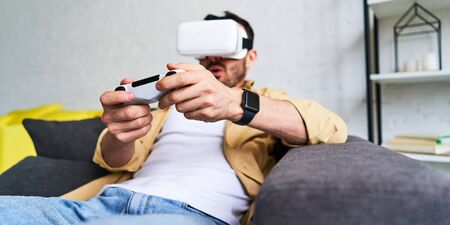 Closeup view of young smiling man in VR glasses playing video game holding joystick, siting on the couch 版權商用圖片