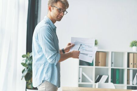 Successful businessman with documents pointing on analytics information