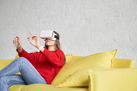 Front view of young smiling woman using virtual reality glasses and showing his hand up 版權商用圖片