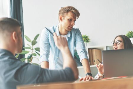Two man and woman working together while sitting at their working place in office