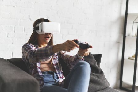 Portrait of amazed excited woman gaming virtual reality glasses with open mouth expression over white wall background. 3d technology, cyberspace concept 版權商用圖片