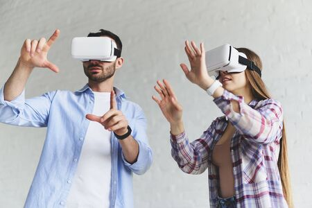 Closeup view of young concentrated couple wear. Virtual reality goggles headset glasses. Happy people using new technology