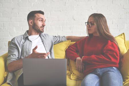 Couple sitting at yellow sofa. Man showing movie on laptop. 版權商用圖片