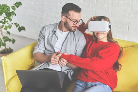 Young cute couple looking at laptop screen and VR glasses sitting on the yellow couch 版權商用圖片