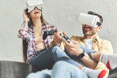 First virtual reality experience for couple, two. Young smiling couple in VR glasses playing video game with laptop on yellow couch while having virtual reality experience