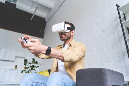 Side view of young smiling man in VR glasses playing video game with joystick, siting on the couch 版權商用圖片