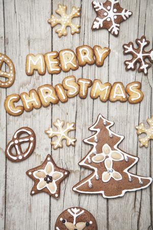 Weihnachtlicher grauer Holz Hintergrund mit Lebkuchen und Merry Christmas Buchstaben