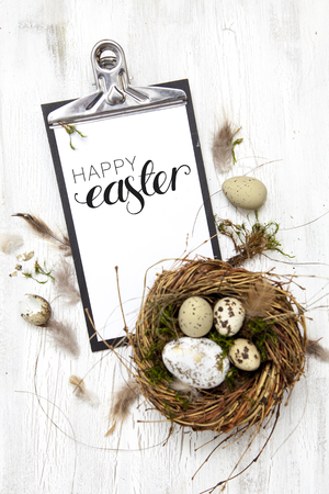 conceptional: beautiful Easter decoration with nest and egg on white wood background Stock Photo
