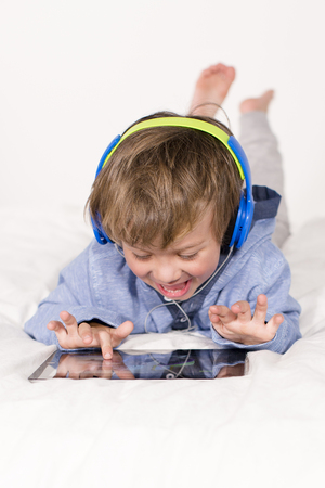 Young boy with tablet and headphones on a bed