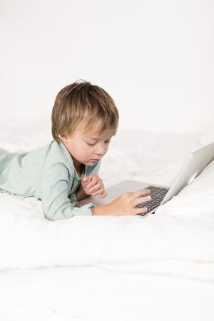 Ein Junge mit Notebook liegt auf einem Bett