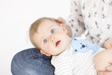 beautiful mother and baby boy sitting in child room