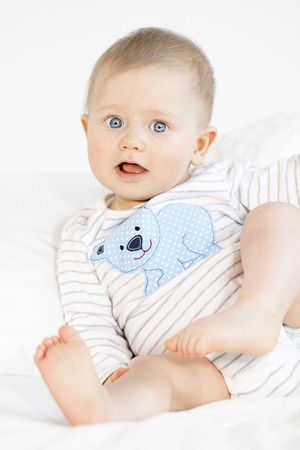 beautiful baby boy lying in bed on white background