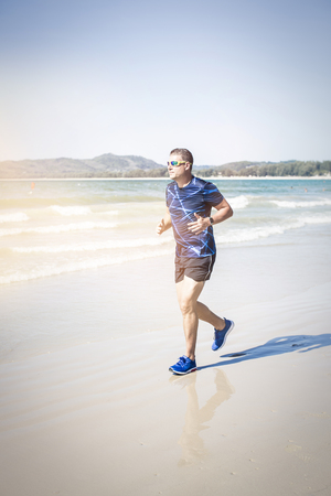 athletic man running on the beach