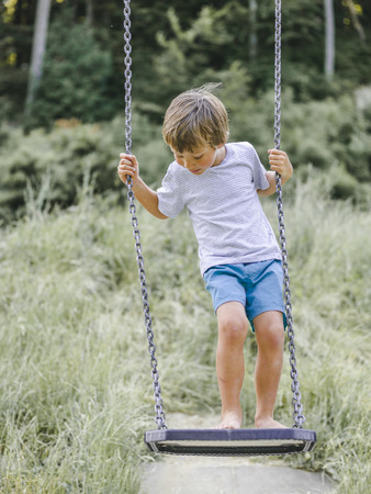 Blond boy playing on a childrens playground and has fun
