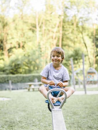 Blond boy playing on a children's playground and has fun Standard-Bild