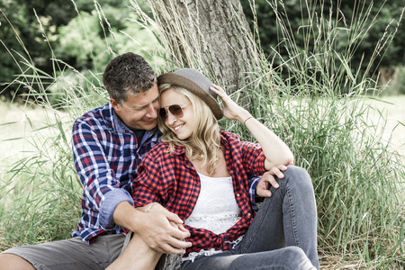 young laughing woman with his happy boyfriend sitting on the meadow