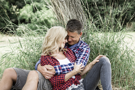 positiv: young laughing woman with his happy boyfriend sitting on the meadow