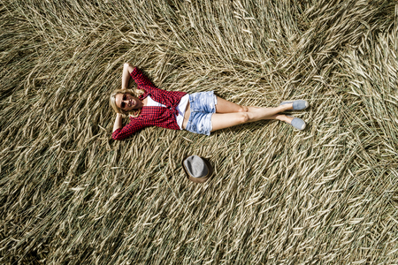 Sexy woman with hat and short jeans and sunglasses is in rye field in summer Standard-Bild