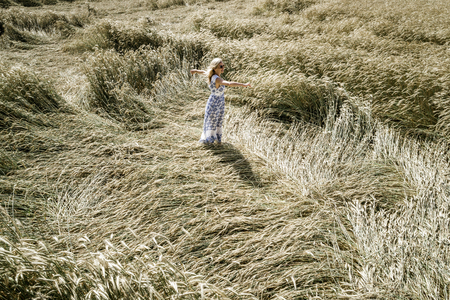 Sexy woman with white, blue dress goes and dances by in rye field