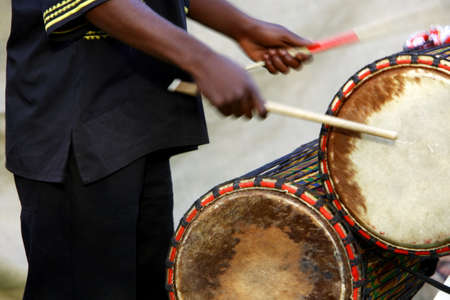African musician playing the drums, late afternoon. Stock Photo