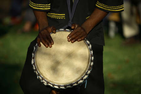 african drums: African musician playing the drums, late afternoon. Stock Photo