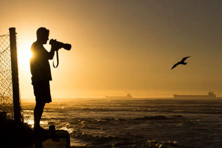 Silhouetted photographer photographing ocean birds at sunset