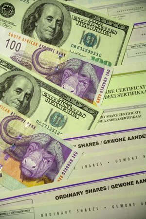 rand: 100 Dollar bills 100 Rand banknotes and various South African share certificates.