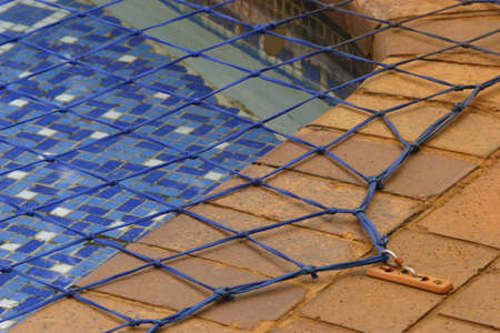 nets: Close up view of a swimming pool net, used to prevent accidental drowning. Stock Photo