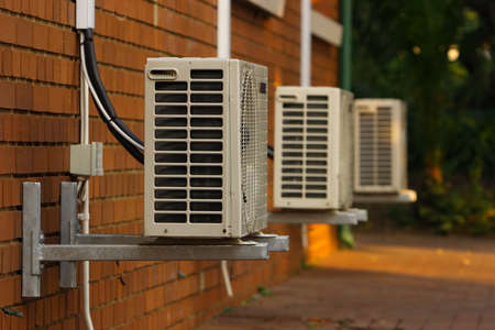air duct: Three external air-conditioner units mounted outside on a wall, focus on the first unit. Stock Photo