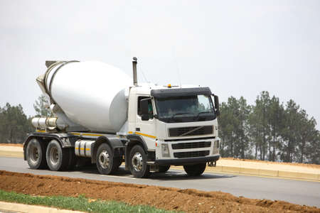 White concrete mixer traveling along a road
