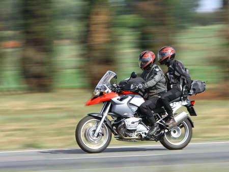 Bike rider and passenger racing through the countryside