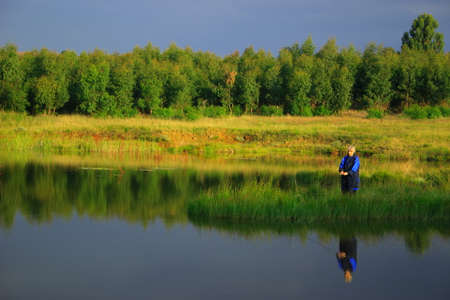 lady fly: Lady fly fishing calm water late afternoon
