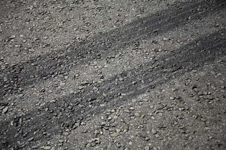 Close up view of rubber tyre tracks on a tar road from vehicles braking harshly photo