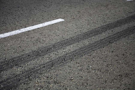 Close up view of rubber tyre tracks on a tar road from vehicles braking harshly