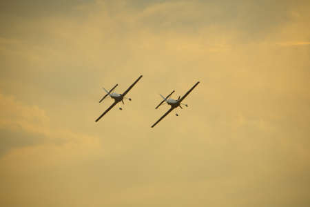 Two light aircraft flying in formation at dusk
