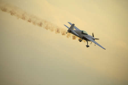 airborne vehicle: Smoking aircraft flying at dusk in a dive