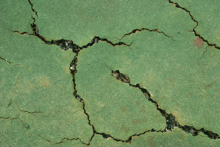 Close up view of a cracked tennis court surface in need of repair.