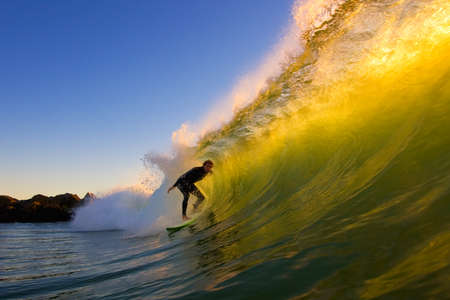 surfing wave: Sunset Surfer Stock Photo