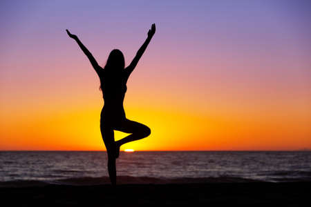 Silhouette of a beautiful Yoga woman at Sunset Фото со стока