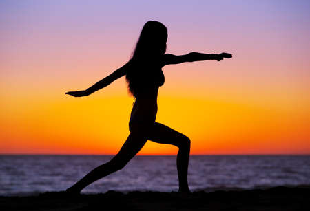 the color of silence: Silhouette of a beautiful Yoga woman at Sunset Stock Photo