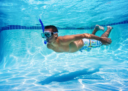 Young Man Swimming in Pool Underwater photo