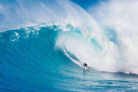 MAUI, HI - MARCH 13: Professional surfer Carlos Burle rides a giant wave at the legendary big wave surf break Jaws during one the largest swells of the winter March 13, 2011 in Maui, HI.