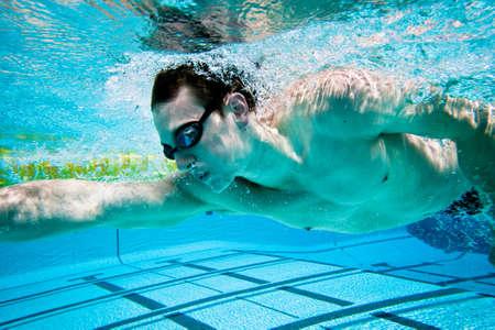 swim goggles: Nadador bajo el agua en piscina