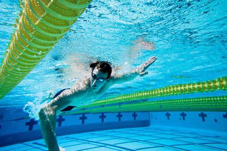 Nadador bajo el agua en piscina Foto de archivo