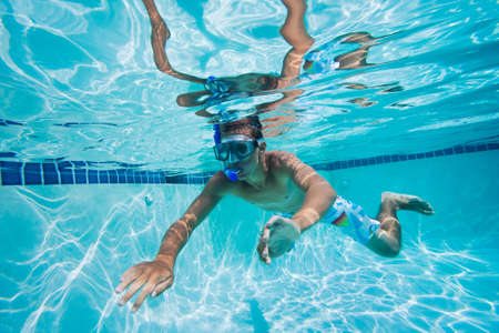 Young Man Swimming Under Water In Pool