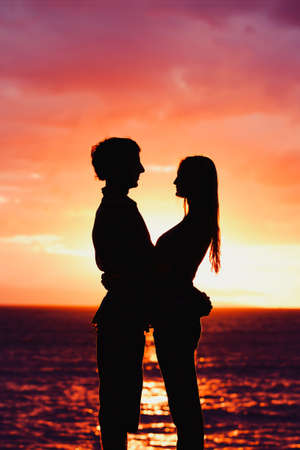Silhouette of Young Romantic Couple at Sunset photo