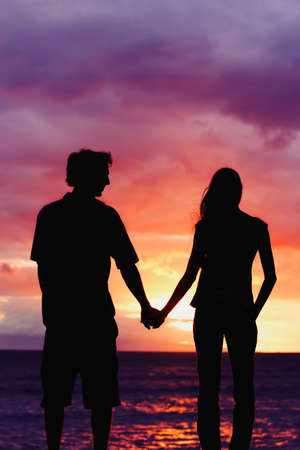 surrender: Silhouette of Young Romantic Couple at Sunset Stock Photo