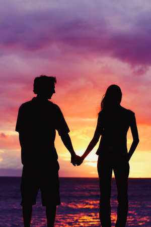 human energy: Silhouette of Young Romantic Couple at Sunset Stock Photo
