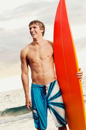 niño sin camisa: surfista profesional la celebración de una tabla de surf